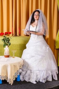 Una sposa ebrea in un abito da sposa bianco con un velo sta nella hall a un tavolo con fiori pregando per una felice vita familiare prima della cerimonia chuppah