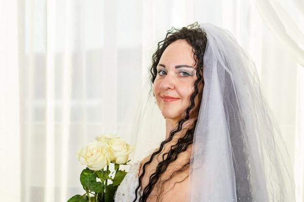 Sposa ebrea con un velo prima della cerimonia della chuppa con un bouquet di rose bianche tra le mani. foto orizzontale