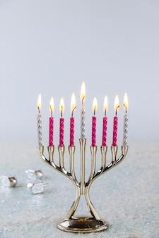 Menorah candeliere ebraico con candele accese su sfondo bianco. festa di hanukkah.