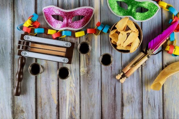 Celebrazione di purim di carnevale ebraico su biscotti hamantaschen, rumorista e maschera con pergamena