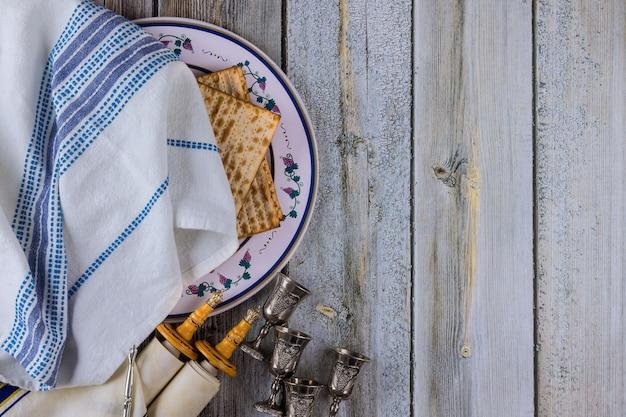 Festa della famiglia ebraica pasqua che celebra i simboli dei rotoli della torah e quattro coppe per il vino