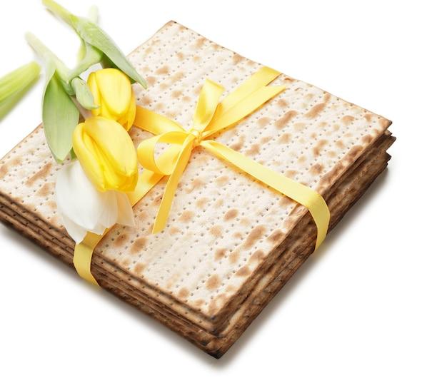 Matza di focaccia ebraica per la pasqua ebraica e fiori sulla superficie bianca