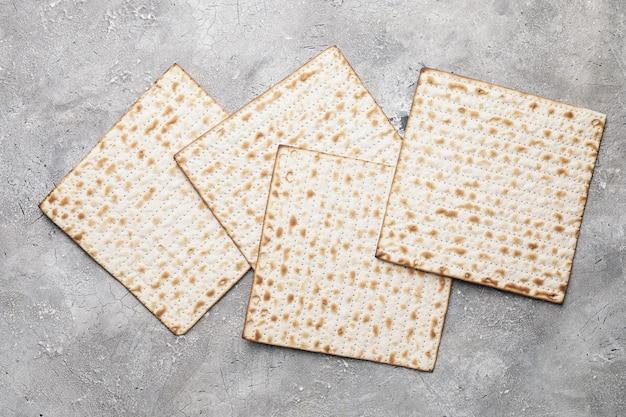 Matza di focaccia ebraica per la pasqua ebraica in uno spazio grigio