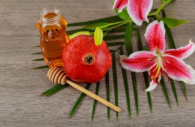 Cibo ebraico, festa ebraica, simbolo di festa, concetto di vacanza jewesh di rosh hashanah - gigli rosa miele di melograno sul tavolo di legno. tradizionale