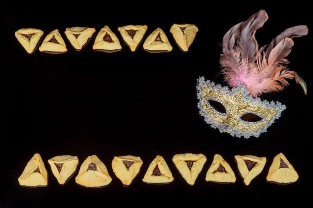 Sfondo festa ebraica con biscotti hamantaschen e maschera di carnevale per purim. copia spazio.