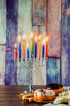 Simboli hannukah delle festività ebraiche - menorah, ciambelle, monete chockolate e dreidels in legno.