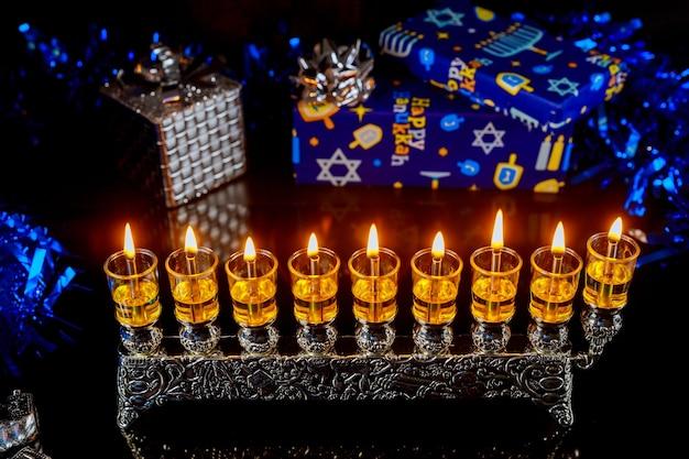 Sfondo festa ebraica hanukkah con menorah in fiamme e scatole regalo.