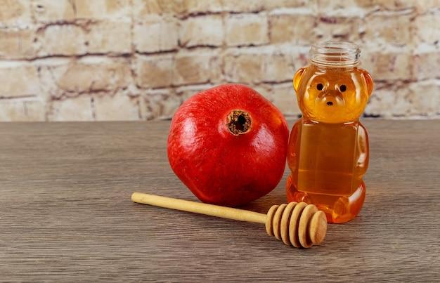 Festa ebraica capodanno ebraico rosh hashana mele miele e melograni su uno sfondo di legno scuro ...