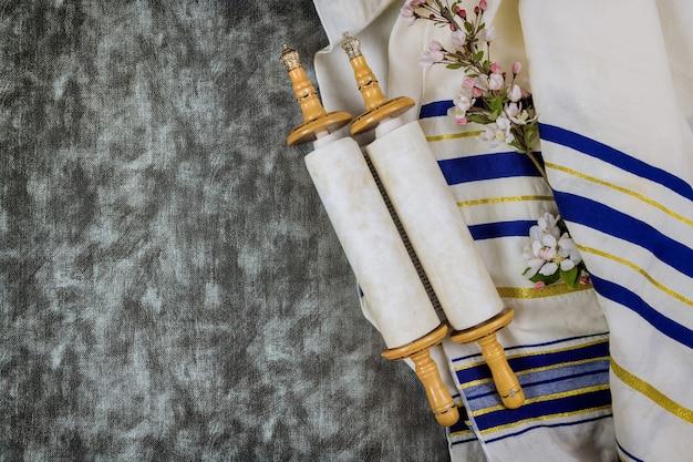 Festività ebraiche, durante gli articoli di preghiera kippa con scialle di preghiera tallit sul rotolo della torah in una sinagoga