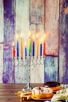 Simbolo ebraico festa ebraica hanukkah con menorah candelabri tradizionali e dreidels in legno spinni...