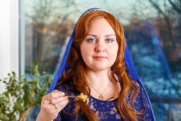 Una donna ebrea con la testa coperta da un mantello blu al tavolo del seder pasquale mangia haroset. foto orizzontale