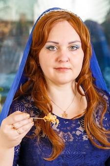 Una donna ebrea con la testa coperta da un mantello blu al tavolo del seder pasquale mangia haroset. foto verticale