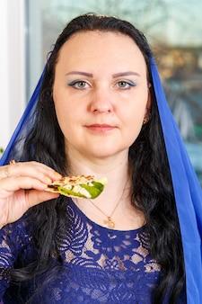 Una donna ebrea con la testa coperta da un mantello blu al tavolo del seder pasquale sta mangiando moror hazeret matzah. foto verticale