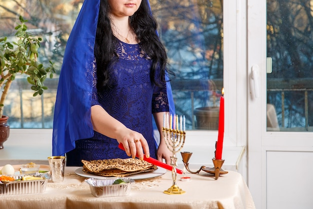 Una donna ebrea con la testa coperta da un mantello blu al tavolo del seder pasquale accende candele da un fuoco ardente. foto orizzontale