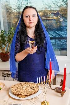 Una donna ebrea con la testa coperta da un mantello blu al tavolo del seder pasquale prepara il kiddush per il vino. foto verticale