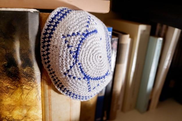 Uno yarmulke ebreo con la stella di david simbolo di israele dimenticato tra i vecchi libri.