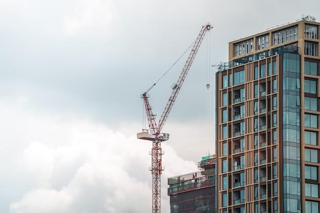 La gru a bandiera sistemata accanto all'edificio completato si sta muovendo per costruire un edificio incompleto dietro con gancio e cavo appesi ad esso.
