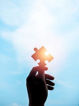 Puzzle contro il cielo blu sullo sfondo con copia spazio, silhouette, stile verticale. mano dell'uomo d'affari che tiene puzzle con la luce del sole. soluzioni aziendali, successo, partnership e concetto di strategia.