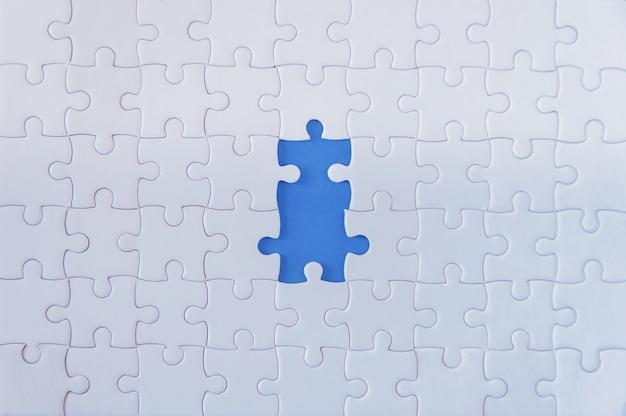 Jigsaw puzzle bianco su sfondo blu.