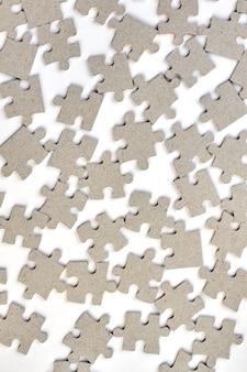Sfondo di puzzle. close up varietà di pezzi di un puzzle grigio su sfondo bianco.