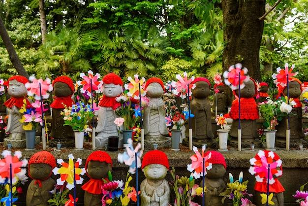 Monumenti o statue jizo con mulino a vento di carta per bambini e decorazioni floreali per bambini non ancora nati al tempio zojoji, tokyo, giappone.