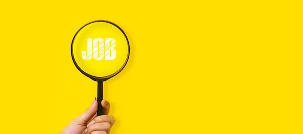 Concetto di ricerca di lavoro, iscrizione e lente d'ingrandimento in mano su uno sfondo giallo