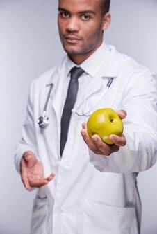 Unisciti a uno stile di vita sano! fiducioso medico africano che allunga la mela verde
