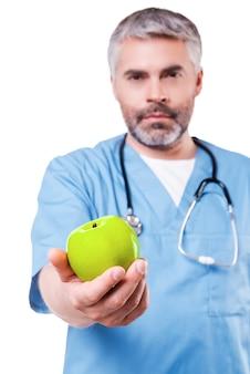 Unisciti a uno stile di vita sano! chirurgo maturo sicuro in uniforme blu che allunga una mela verde mentre stando isolato su white