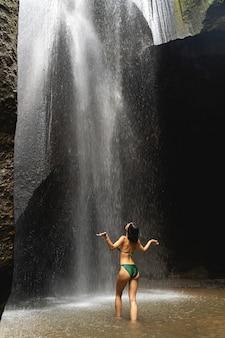 Unisciti a me. gentile ragazza bruna che indossa il costume da bagno e in piedi davanti alla cascata, natura selvaggia