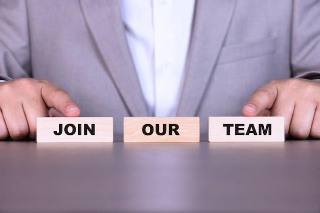 Unisciti al nostro team, concetto di business, tecnologia. il testo è scritto su blocchi di legno sullo sfondo di un uomo d'affari.