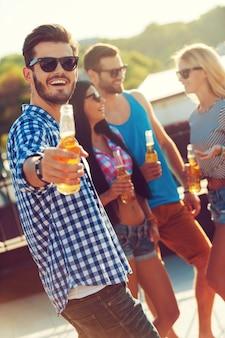 Unisciti a noi! giovane allegro che allunga una bottiglia di birra e guarda la telecamera mentre tre persone parlano tra loro in sottofondo
