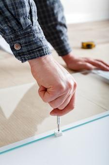 Il falegname raccoglie i mobili utilizzando un cacciavite per utensili manuali. il carpentiere raccoglie un armadio per mobili bianco. montaggio mobili con cacciavite. traslochi, ristrutturazioni, riparazioni e ristrutturazioni di mobili.