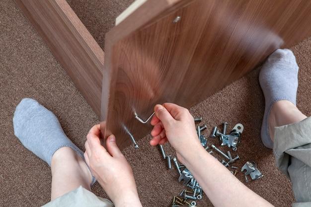 Assemblaggio di mobili da falegname a casa utilizzando una chiave a brugola.