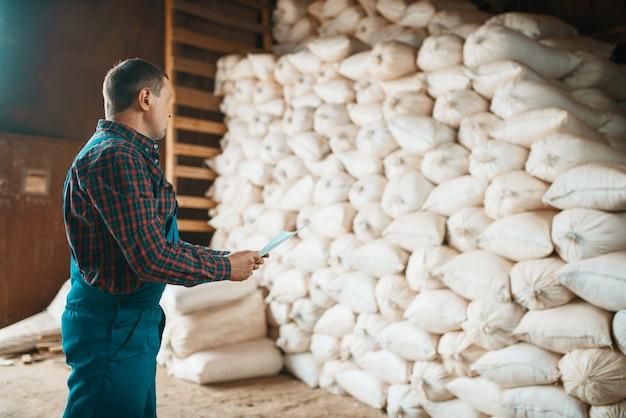 Falegname in uniforme controlla sacchi di segatura su mulino, macchine per la lavorazione del legno, industria del legname, carpenteria. lavorazione del legno in fabbrica, segatura forestale nel deposito di legname