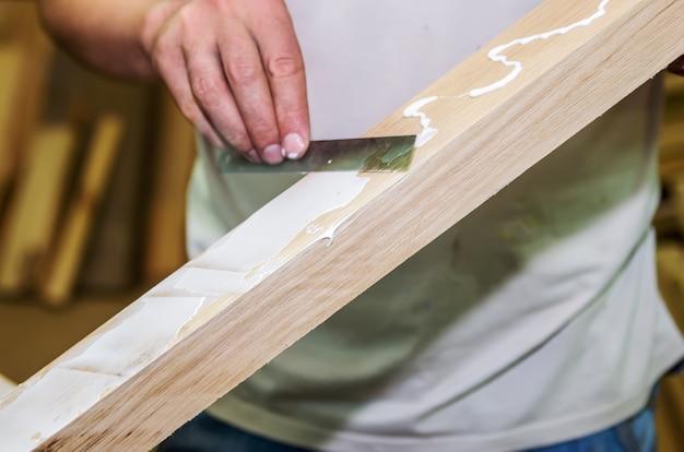 Lavori di falegnameria. applicare l'adesivo su una superficie di legno