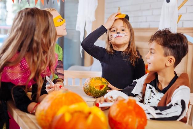 Unirsi agli amici. piccola ragazza carina dai capelli scuri che indossa un costume da gatto per halloween che si unisce ai suoi amici che colorano le zucche