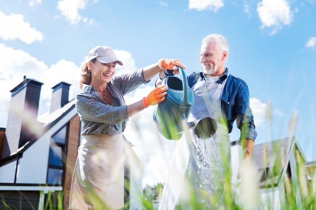 Unire il marito. sorridente bella donna che indossa il berretto con visiera sentirsi adorabile mentre si unisce a suo marito che innaffia le piante