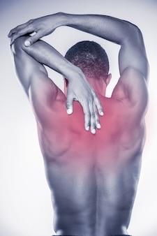 Dolori articolari. vista posteriore di un giovane africano muscoloso che si tocca il collo e il gomito mentre si trova in piedi su sfondo grigio