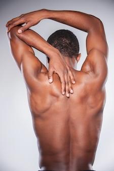 Dolori articolari. vista posteriore di un giovane africano senza camicia che si tocca il collo e il gomito mentre si trova su uno sfondo grigio