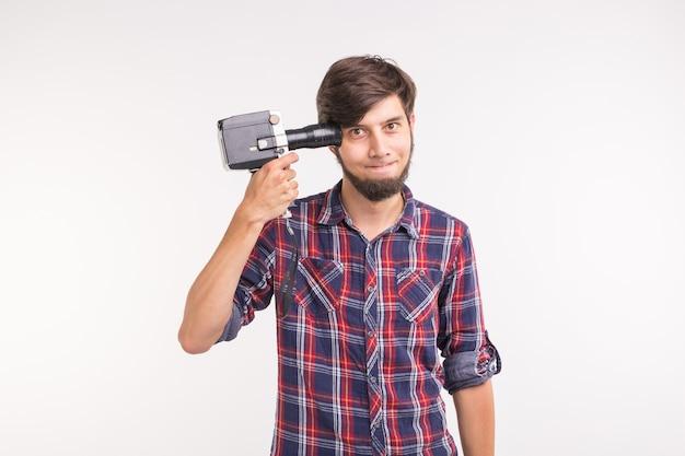 Concetto di scherzo, foto e gesto - giovane uomo sciocco divertente che posa con la macchina fotografica vicino alla sua testa su bianco