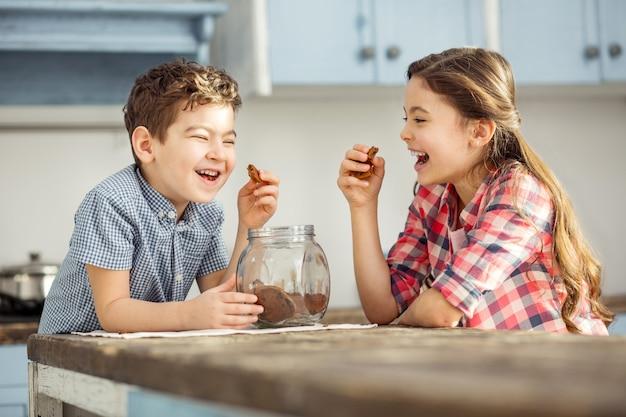 Scherzando. carino felice piccolo fratello dai capelli scuri e sorella che ride e mangia i biscotti mentre era seduto al tavolo