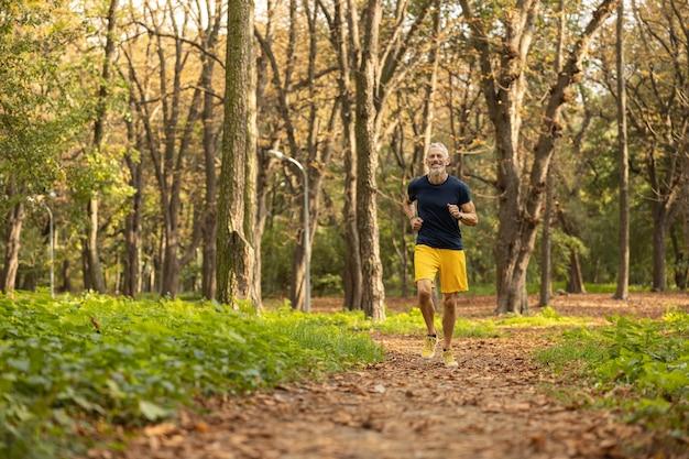 Jolly maschio barbuto che va a fare jogging nel bosco