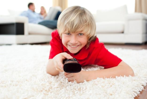 Ragazzo allegro che guarda la tv che si trova sul pavimento