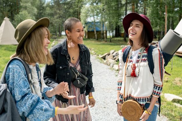 Ragazze allegre con roba in piedi sul sentiero e ridendo insieme nel campeggio nella foresta