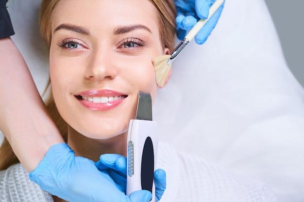 La giovane donna allegra si sta rilassando mentre il cosmetologo sta facendo la pulizia ad ultrasuoni per lei.