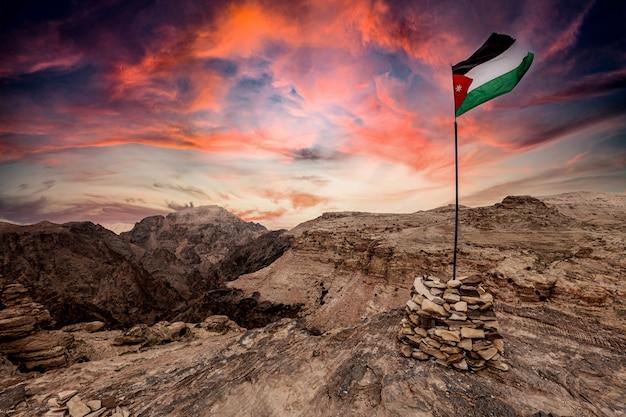 Bandiera della giordania sulle montagne vicino a petra. cielo spettacolare al tramonto.