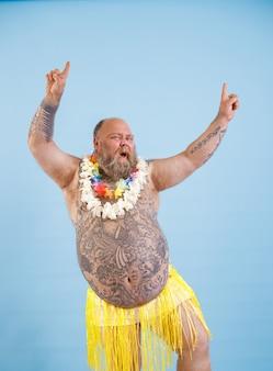 Jouful uomo grassoccio con petto nudo in gonna di erba gialla si diverte su sfondo azzurro