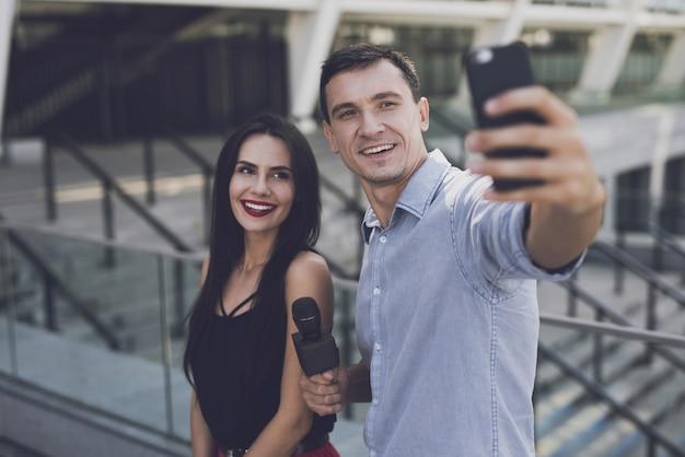 Un giornalista fa un selfie con una ragazza.