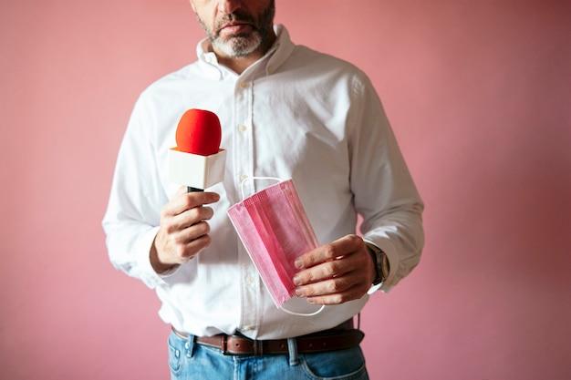 Giornalista con maschera e microfono in mano sulla parete rosa