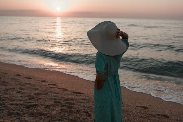 Viaggio al mare una ragazza con vestito e cappello cammina lungo la spiaggia un turista cammina lungo il mare...